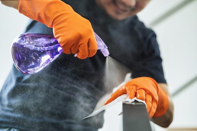 Pulvérisation à la main d'un homme asiatique dans l'escalier de la maison pour le nettoyage par tour lors d'une épidémie et d'une pandémie de covid19