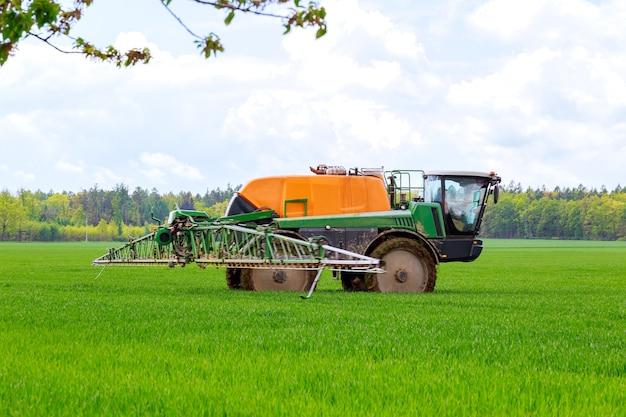 Pulvérisation de pesticides sur de jeunes blés au champ à l'aide d'un pulvérisateur tracteur.