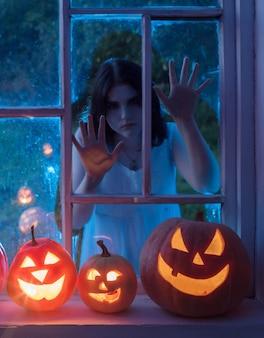 Pumpins d'halloween sur le rebord de la fenêtre avec fenêtre à l'extérieur du fantôme