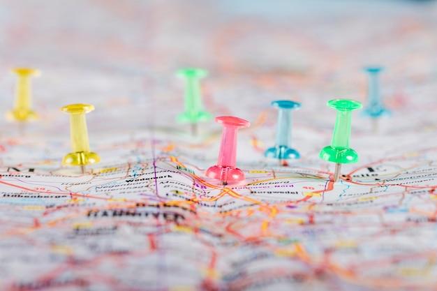 Punaises multicolores pointant vers des destinations planifiées sur la carte