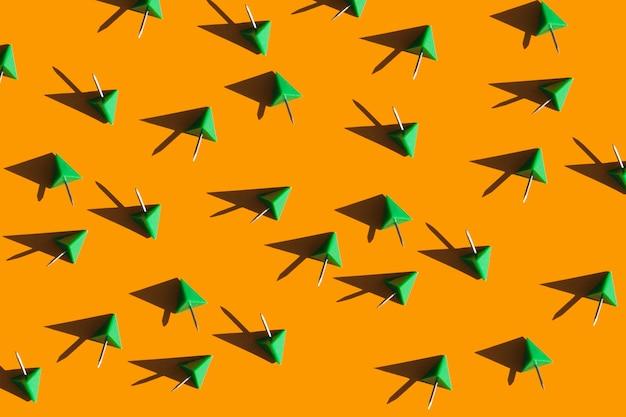 Punaises vertes sur fond orange modèle de fournitures scolaires et de bureau