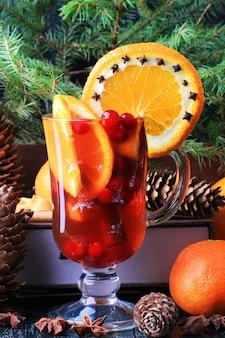Punch chaud avec des canneberges orange et des épices cônes de sapin de noël vintage vieux fond en bois de style rustique