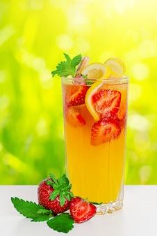 Punch rafraîchissant aux fraises, citron et menthe sur fond ensoleillé flou.