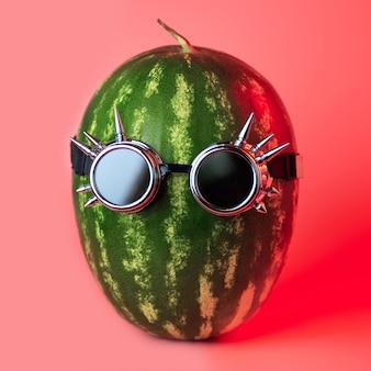 Un punk de pastèque dans des lunettes à bascule sur rose
