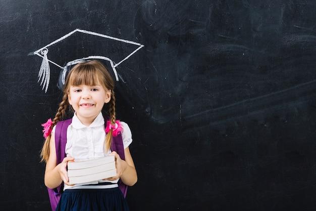 Pupille fille avec des livres en maître chapeau