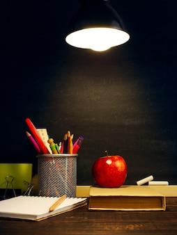 Le pupitre du professeur sur lequel repose le matériel d'écriture, un livre et une pomme, le soir sous la lampe.