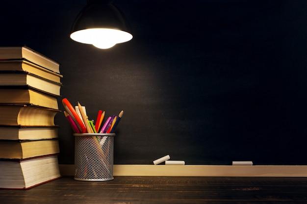Le pupitre du professeur sur lequel repose le matériel d'écriture, le soir sous la lampe.