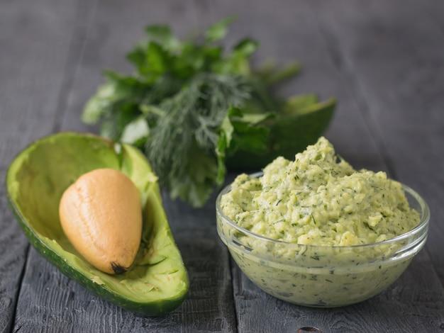 Purée d'avocat à la crème au persil, à l'aneth et à l'ail dans un bol sur une table vintage. le plat est un régime végétarien.