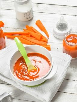 Purée de carottes bébé avec du lait dans une bouteille