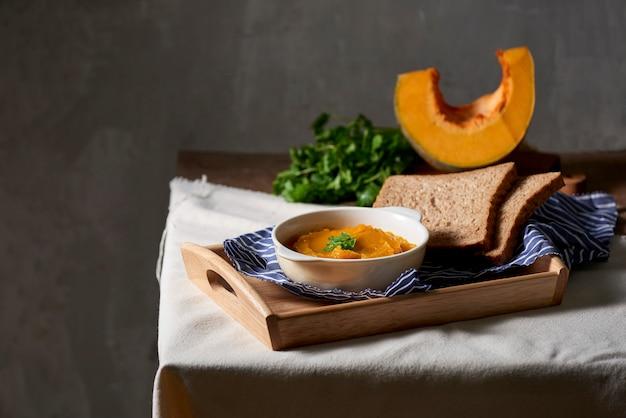 Purée de citrouille sur une table en bois rustique.