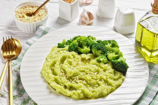 Purée de pommes de terre au brocoli saupoudrée d'amandes hachées servie avec des fleurons de brocoli cuits à la vapeur sur une assiette sur une table en bois blanc, vue horizontale d'en haut