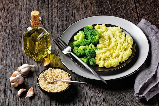 Purée de pommes de terre au brocoli saupoudrée d'amandes hachées servie avec des fleurons de brocoli cuits à la vapeur sur une plaque noire sur une table en bois sombre