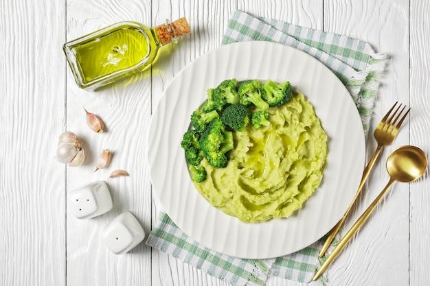 Purée de pommes de terre au brocoli servie avec des fleurons de brocoli sur une assiette sur une table en bois blanc, vue horizontale d'en haut, mise à plat