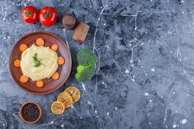 Purée de pommes de terre et carottes tranchées sur une assiette à côté de légumes et bols d'épices, sur la table bleue.