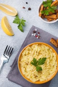 Purée de pommes de terre avec des herbes, des croûtons et du citron dans une assiette sur des serviettes.