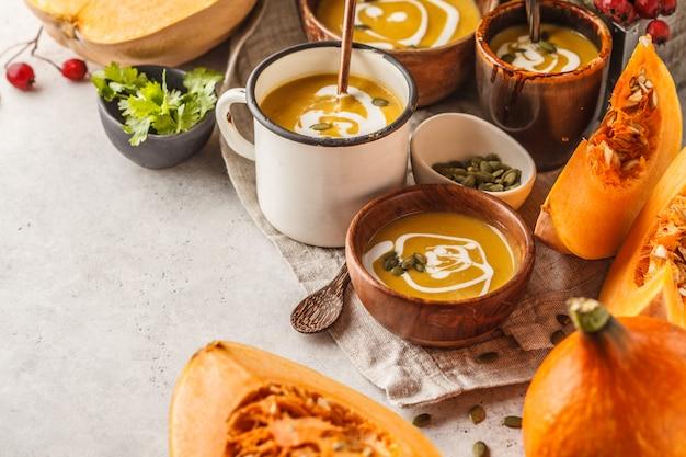 Purée de potiron d'automne à la crème dans des tasses, le paysage d'automne. concept de nourriture végétalienne saine.
