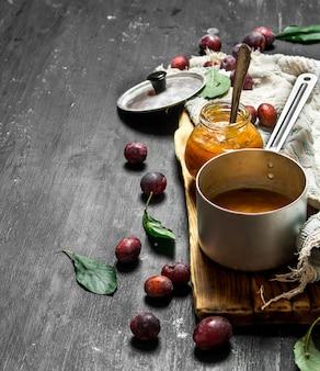 Purée de prunes mûres dans une petite casserole. sur un tableau noir.