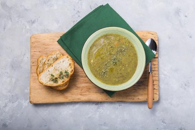 Purée de soupe au brocoli avec servi avec des tranches de baguette grillées et de l'huile de folive sur une planche de bois vue de dessus, flatlay, copy space
