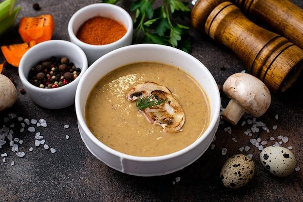 Purée de soupe aux champignons dans une assiette avec des ingrédients sur les côtés sur une table noire.