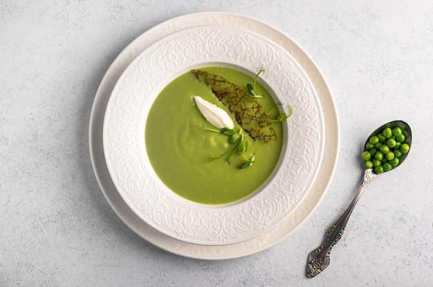 Purée de soupe maison de pois verts, lait de coco avec tuil et quenelle au fromage en plaque blanche sur