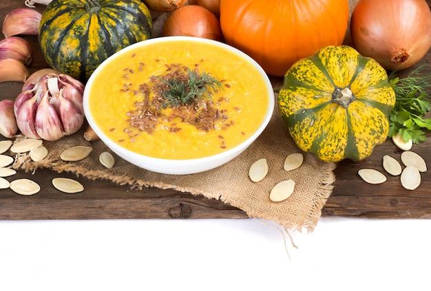 Purée de soupe de potiron fraîche dans un bol et des pampkins crus sur une table en bois se bouchent