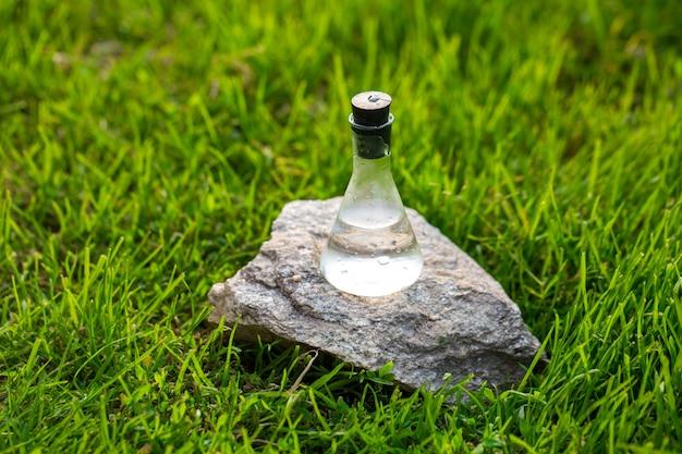 Purger l'eau dans une fiole sur la pelouse en fleurs. échantillon d'eau pour une expérience environnementale.