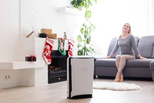 Purificateur d'air dans un salon, femme travaillant avec un ordinateur portable avec filtre pour salle blanche