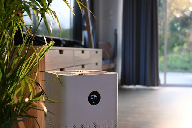 Purificateur d'air avec écran numérique et plante d'intérieur dans le salon pour un air frais et une vie saine.