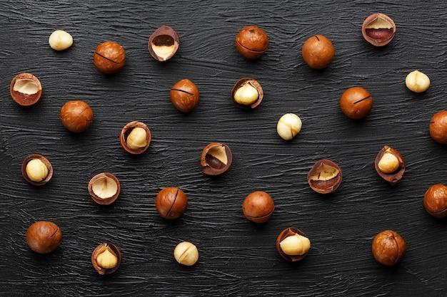 Purifié et coquille répète les noix de macadamia sur fond de pierre texturale noir. concept d'alimentation saine
