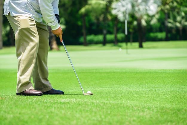 Putter de golf mettant les athlètes à frapper une balle de golf dans le trou pour atteindre le but