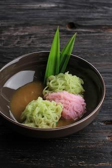 Putu mayang ou petulo, collation javanaise traditionnelle indonésienne faite de brins de farine de riz enroulés en boule avec du colorant alimentaire, servi avec du lait de coco et du sirop de sucre de palme.