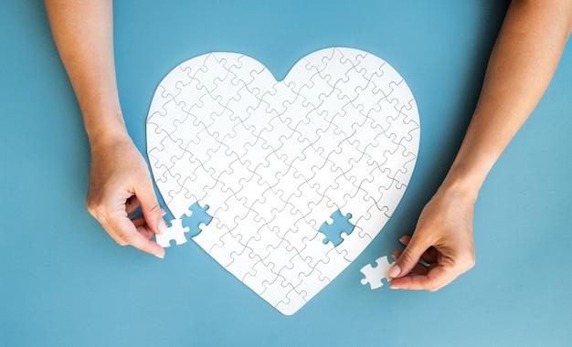 Puzzle blanc dans les mains en forme de coeur avec des détails blancs de puzzle sur bleu