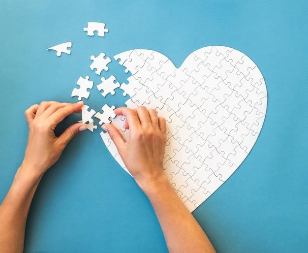 Puzzle blanc en forme de coeur détails blancs du puzzle sur bleu