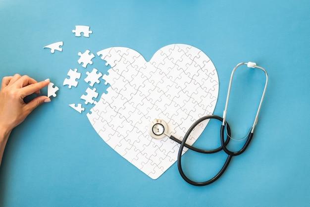 Un puzzle blanc en forme de coeur relie les détails blancs du puzzle sur le bleu