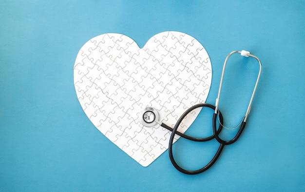 Puzzle blanc en forme de coeur et stéthoscope sur bleu