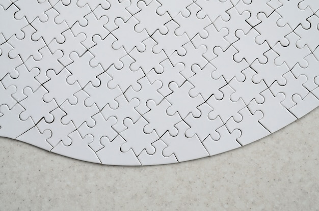 Un puzzle blanc de forme complète repose sur une surface en pierre traitée.