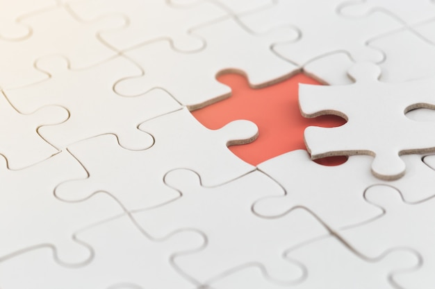 Puzzle blanc avec pièce manquante de couleur orange.