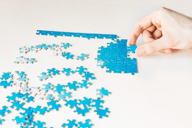 Puzzle bleu à la main. main tenant la pièce du puzzle sur fond blanc. pièce jointe puzzle, connexion d'affaires, éducation, société et travail d'équipe