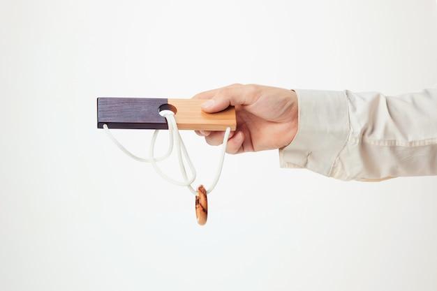 Le puzzle en bois jouet en main isolé sur mur blanc