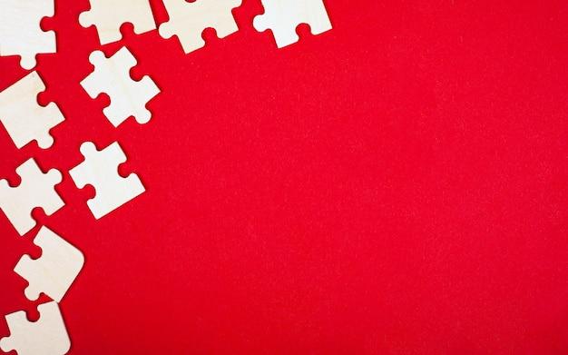 Puzzle en bois mosaïque sur fond rouge vue de dessus gros plan copie espace.