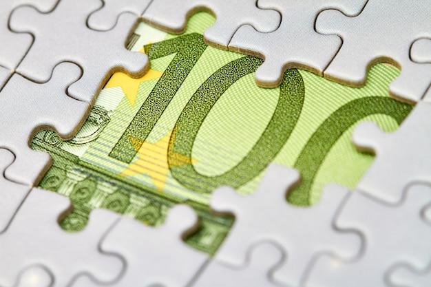 Puzzle euro, concept d'entreprise de solution. billet de cent euros et pièces de puzzle. gros plan, mise au point sélective