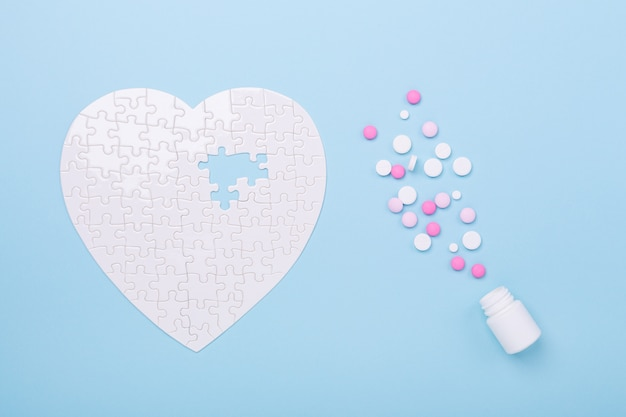 Puzzle en forme de coeur blanc et pilules roses sur