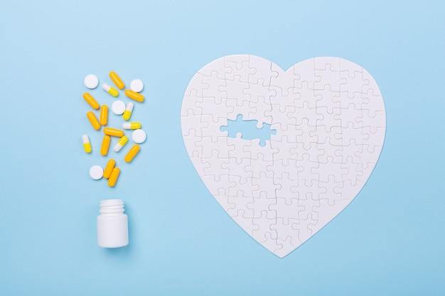 Puzzle en forme de pilules blanches et jaunes de coeur sur bleu