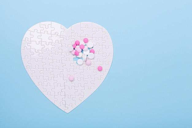 Puzzle en forme de pilules blanches et roses de coeur sur bleu