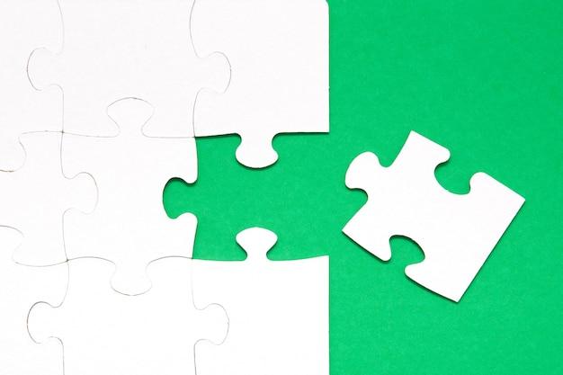 Puzzle inachevé un fond vert une pièce manque