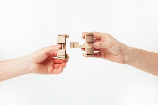 Puzzle en main isolé sur mur blanc