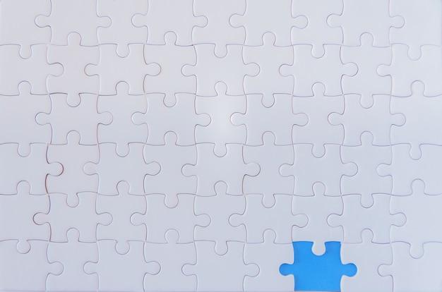 Puzzle avec une pièce manquante révélant le fond bleu