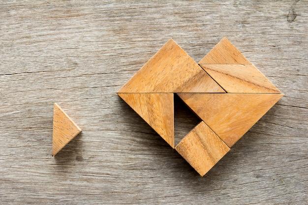 Puzzle tangram attendre pour remplir en forme de coeur sur la table en bois