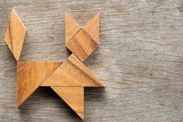 Puzzle de tangram chinois en forme de chat sur fond en bois