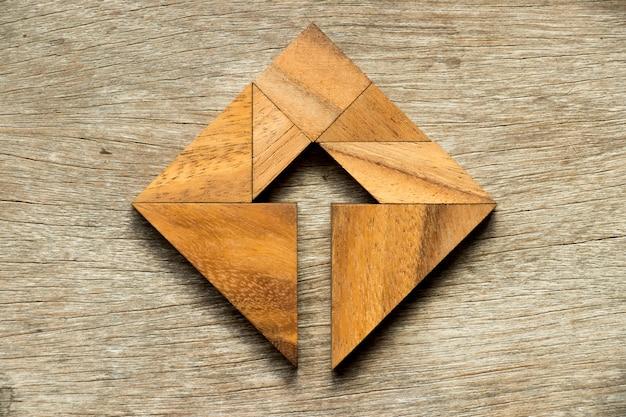 Puzzle tangram en forme carrée avec le symbole de la flèche à l'intérieur sur fond de bois